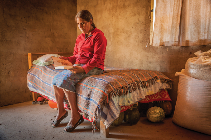 Tepehuan woman sitting on her bed and reading the Bible