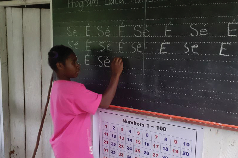 Elseng girl practices writing on a chalkboard