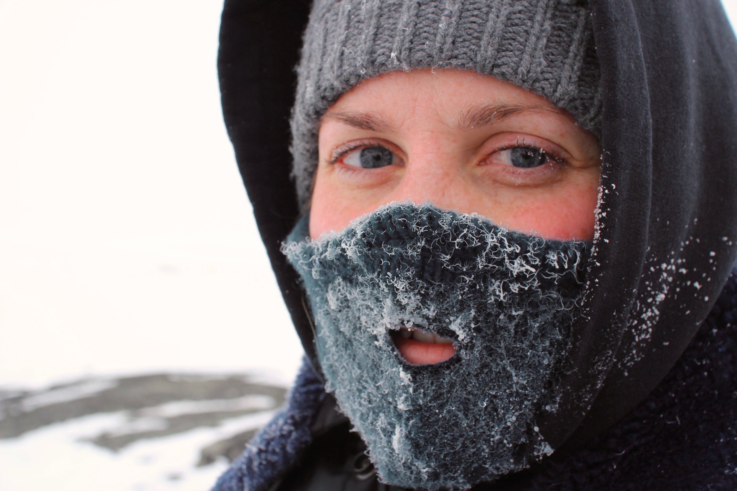 woman wearing hat, hood and mask against the cold