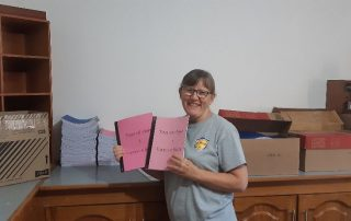 a missionary holding up newly printed books