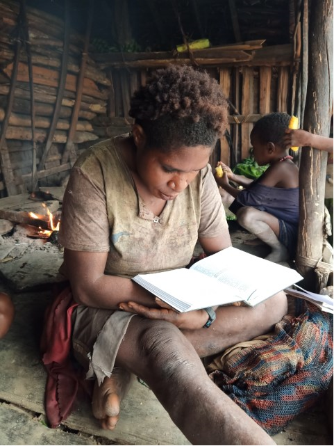 Moi woman reading Bible in a hut