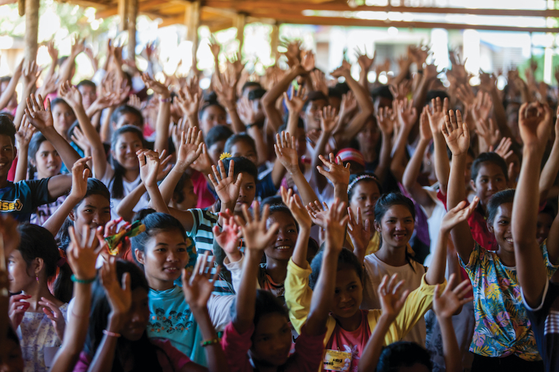 young people holding their hands up