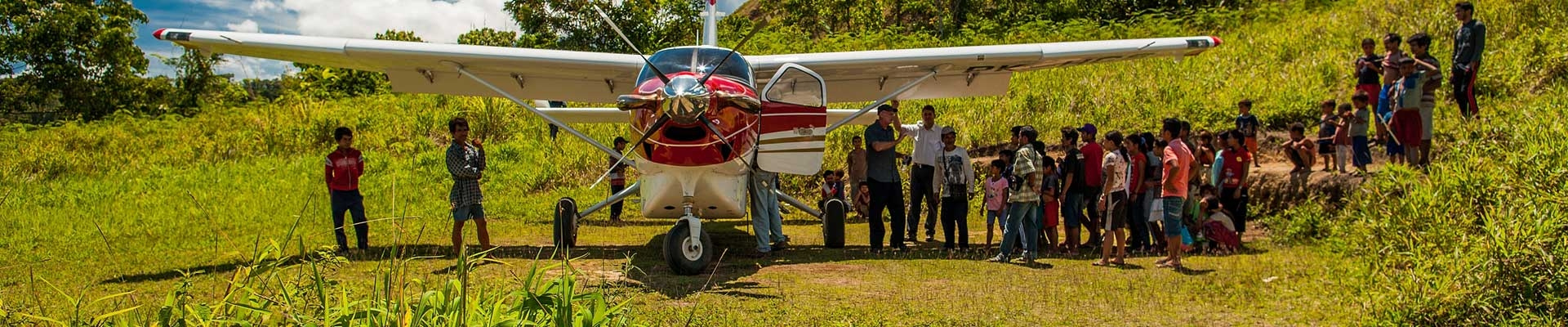 tribal people gathered to welcome missionaries at the air strip