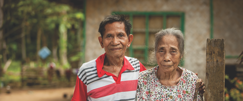 smiling elderly couple with house and forest behind them