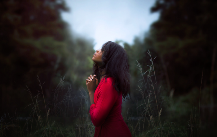 woman clasping her hands in prayer while standing in a clearing
