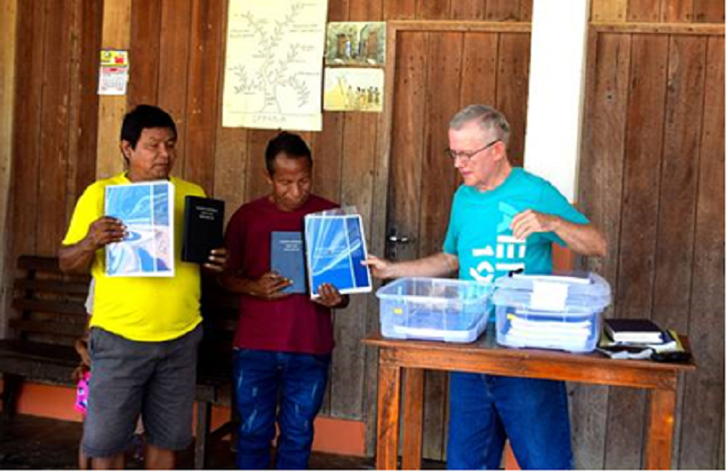 missionary with friends holding up Bible portions for dedication ceremony