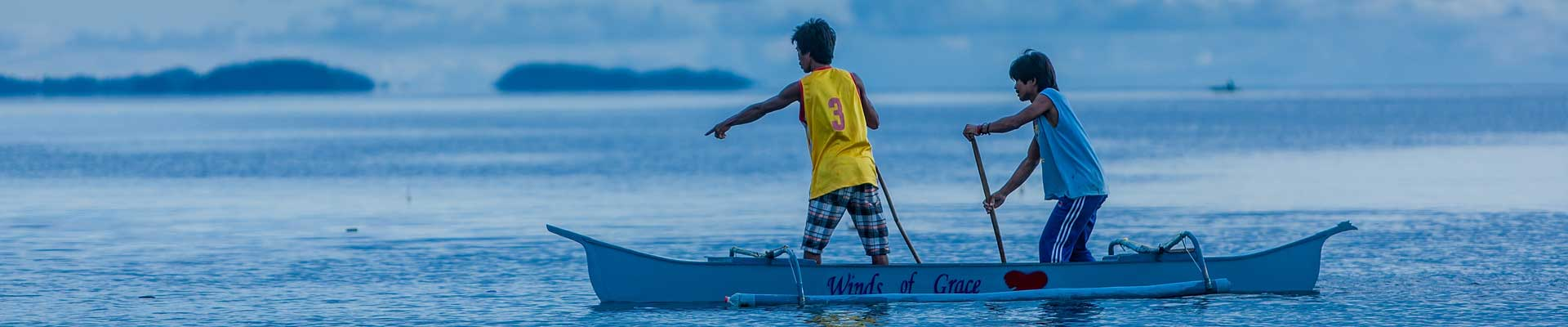 two Filipino men in an outrigger canoe