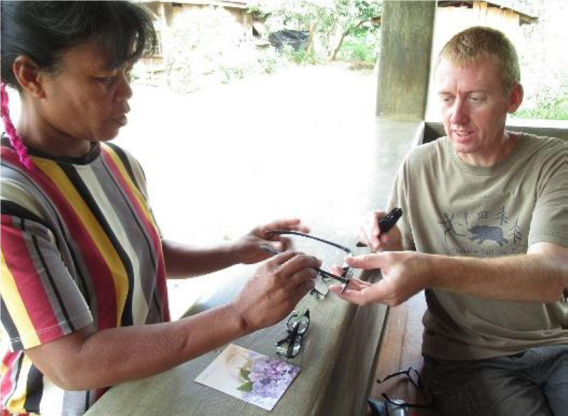Grant Bayfield handing glasses to Manobo woman