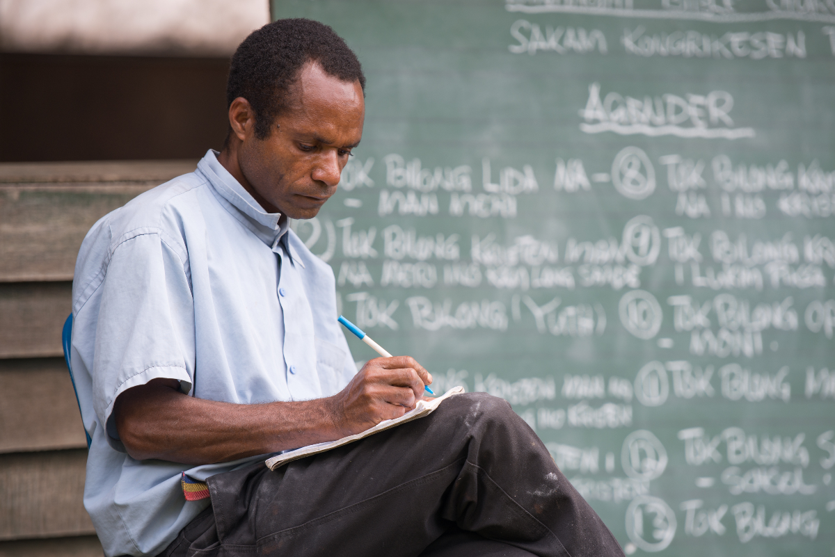 Dinangat man with a notebook in front of a chalk board