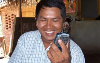 man smiles while holding audio Bible