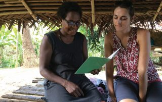 Kaje woman learning to read with missionary